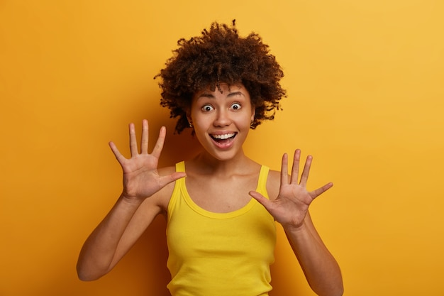 Positive dark skinned woman raises palms, feels joyful, has playful mood, gazes with funny expression, wears casual shirt, isolated over yellow wall. people, emotions and happiness concept