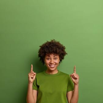 La donna dalla pelle scura positiva mostra lo spazio della copia sopra, punta il dito indice verso l'alto, dimostra simpatia, suggerisce una buona idea, isolata sul muro verde. persone e concetto di promozione