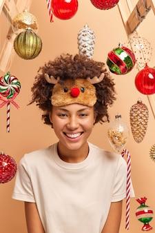 긍정적 인 어두운 피부를 가진 여자는 사슴 수면 마스크를 착용하고 캐주얼 티셔츠 미소는 겨울 휴가 포즈를 광범위하게 기다립니다.