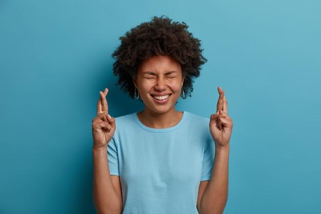 アフロの髪型を持つポジティブな暗い肌の女性は、幸運のために指を交差させ、目を閉じて広く笑顔で、夢が叶うと信じて、青い背景で隔離のカジュアルなtシャツを着ています