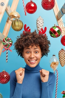 Positive dark skinned woman with curly hair in casual turtleneck clenches fists anticipates for miracle prepares for christmas holidays dressed casually poses indoor over new year toys. festive event.
