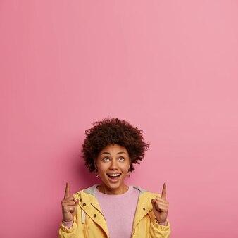 곱슬 헤어 스타일을 가진 긍정적 인 어두운 피부의 여성, 위의 앞쪽 손가락을 가리키고 천장에 무언가를 보여줍니다.
