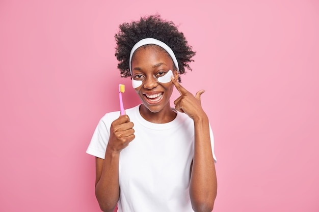 Positive dark skinned woman with natural curly hair applies beauty pads under eyes holds toothbrush undergoes daily hygienic routine