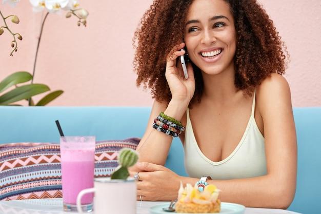La giovane donna afroamericana dalla pelle scura positiva ha una conversazione piacevole tramite un moderno smart phone, ricrea nella caffetteria, beve frullato e mangia la torta