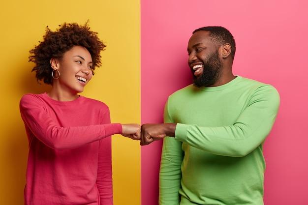 긍정적 인 어두운 피부의 젊은 여성과 남성이 주먹을 부딪 히고, 한 팀이되기로 동의하고, 서로를 행복하게 바라보고, 완료된 작업을 축하하고, 분홍색과 녹색 옷을 입고, 실내 포즈를 취하고, 성공적인 거래를합니다.