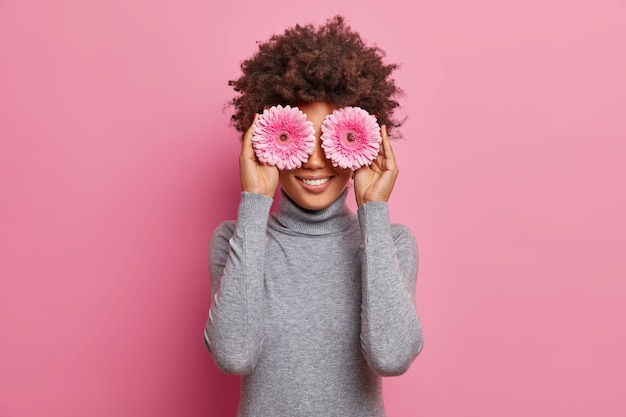 Positive dark skinned young woman enjoys spring day, holds pink gerbera flowers on eyes