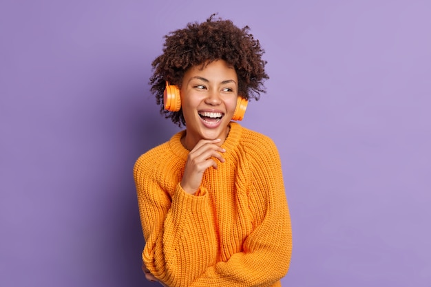 La giovane donna dalla pelle scura positiva ascolta la musica in cuffia tiene il mento e sorride soddisfatto concentrato da parte si sente felicissimo indossa un maglione arancione lavorato a maglia caldo