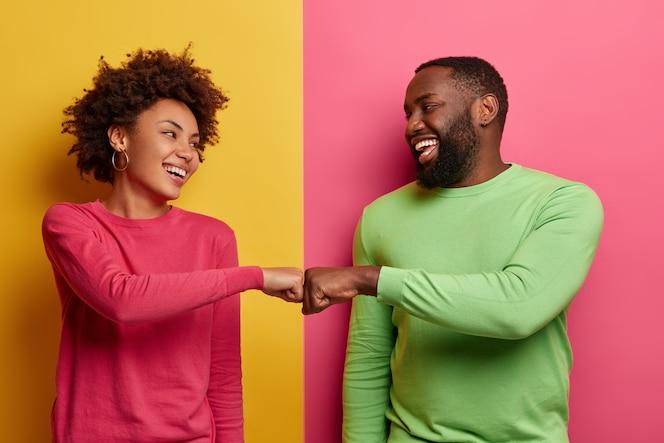 La giovane donna e l'uomo dalla pelle scura positiva sbattono i pugni, accettano di essere una squadra, si guardano felici l'un l'altro, celebra il compito completato, indossa abiti rosa e verdi, posa al coperto, ha un accordo di successo