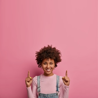 ポジティブな暗い肌の若い女性は人差し指を上に向けます