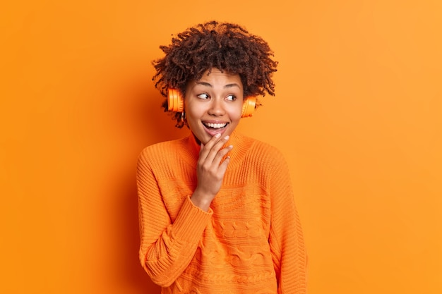 Positive dark skinned young woman with curly hair listens audio track
