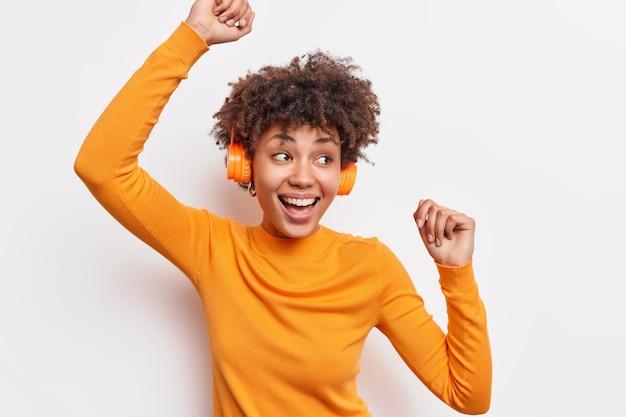 巻き毛のポジティブな暗い肌の若い女性は腕を上げて気楽に踊りますカジュアルなジャンパーの笑顔は広く白い壁に隔離されたリズムで音楽の動きのすべてのビットをキャッチします