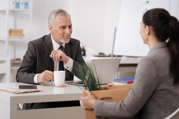 긍정적 인 기쁘게 수염 난 남자 의상을 입고 오른손에 컵을 유지하는 테이블에 팔을 올려 새로운 동료를보고