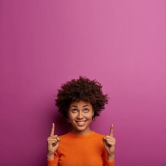 Положительно обрадованная кудрявая женщина получает новую идею для развития, показывает указательными пальцами выше, показывает место для текста на фиолетовой стене, приятно улыбается, позирует в помещении, демонстрирует вам приятное предложение
