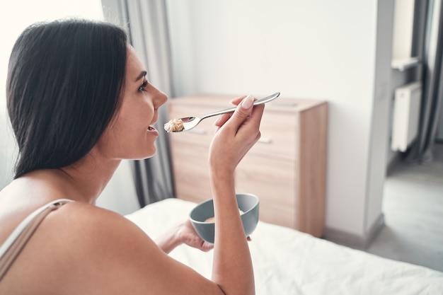 彼女の部屋で朝食をとっている間、左手にボウルを持っている前向きな喜びの女性