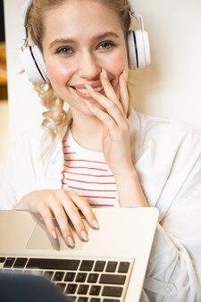 Позитивный довольный человек женского пола с улыбкой на лице во время прослушивания музыки