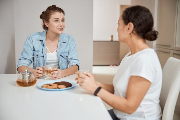 Положительно довольные женщины пьют чай и едят печенье, проводят утро дома