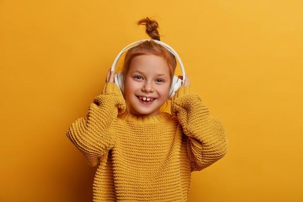 Положительно обрадованная рыжая девочка слушает аудиозапись в наушниках, увлекается любимым хобби, одетая в большой вязаный свитер, изолирована над желтой стеной. дети, музыка и развлечения
