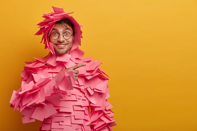 Positive delighted man points at product, advertises items for office, glad about advertisement, wears round spectacles, sticky notes over body and head, has happy smile, isolated on yellow wall