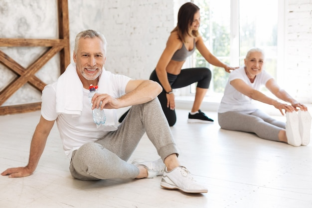 Positive delighted mature man keeping smile on his face and putting right hand on the floor while posing on camera