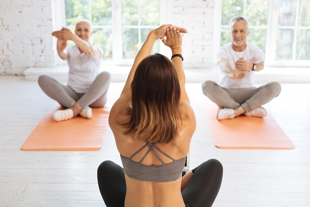 Positive delighted people sitting on mats and repeating exercises after their tutor while keeping smile on faces
