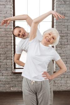 Позитивно довольные люди в белых футболках, держащие руки за талию, сохраняя улыбку на лицах