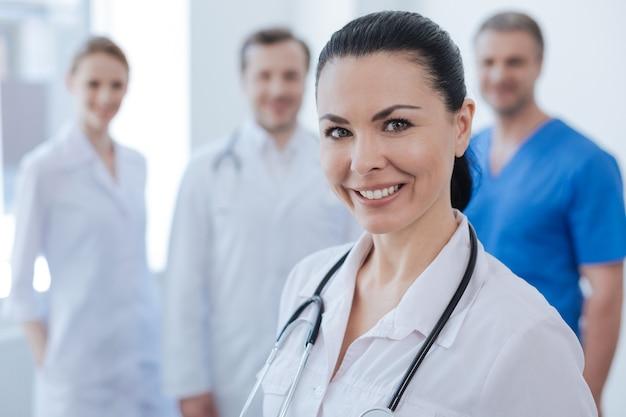 긍정적으로 기뻐하는 유능한 의료진이 병원에 서서 기쁨을 표현하고 동료들은 뒤에 긍정을 표현합니다.