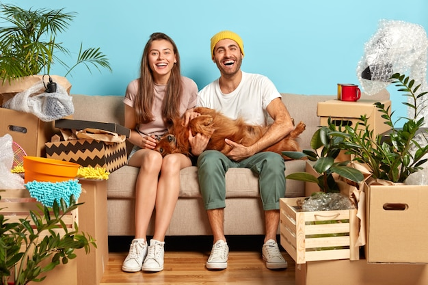 Positive delighted woman and man play with their favourite dog, pose on sofa