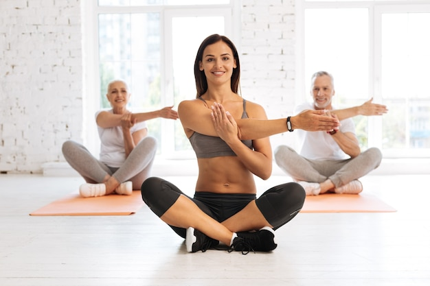 Positive delighted woman in sport clothes sitting with crossed legs and stretching her arm, having fitness bracelet on right hand
