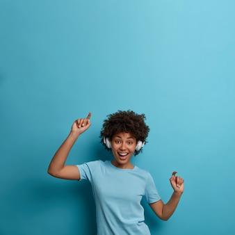 La giovane donna afroamericana felice positiva gode della melodia della musica, indossa le cuffie senza fili, si muove con il ritmo della canzone, ha un umore felice, isolato sul muro blu, copia lo spazio sopra. riposo, stile di vita