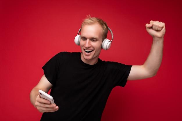 黒のtシャツと立っている白いヘッドフォンを身に着けているポジティブで楽しいハンサムな金髪の若い男