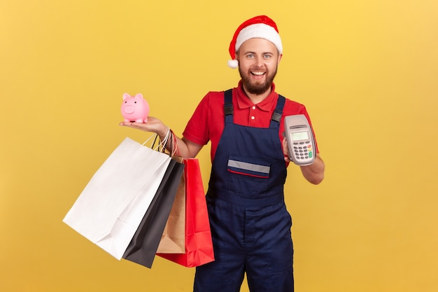 Positive delivery man in uniform and santa claus hat holding paper shopping bags, payment terminal and piggy bank, paying contactless and saving money, cashback. indoor isolated on yellow background