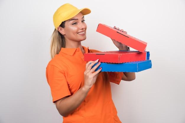 Donna di consegna positiva che apre la scatola della pizza.