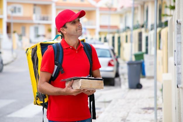 Положительный доставщик держит посылку с буфером обмена и ждет получателя на открытом воздухе. красивый кавказский мужчина с желтым рюкзаком, доставляя заказы людям. служба доставки и почтовая концепция