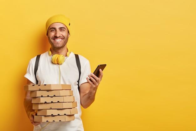 Положительный доставщик с коробками для пиццы