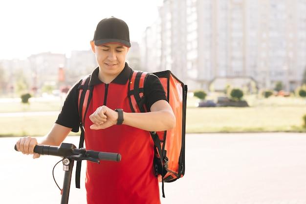 긍정적인 배달원 직원은 온라인 주문 고객 고객이 웃고 있는 남자 택배 음식을 배달합니다.
