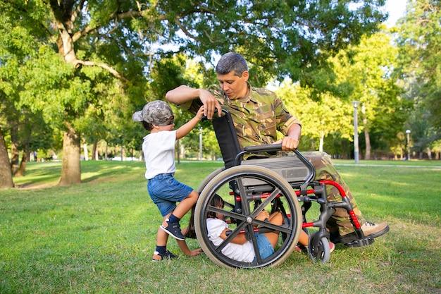 Papà militare disabile positivo che gode del tempo con i bambini nel parco. bambini che giocano con la sedia a rotelle sull'erba. veterano di guerra o concetto di disabilità