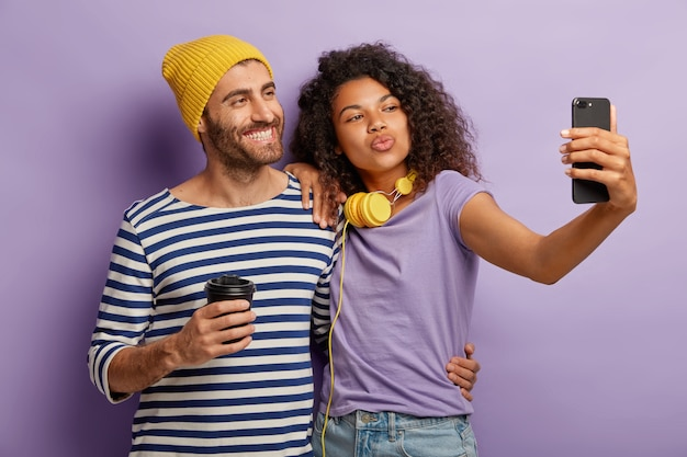 Positive diverse couple pose together for making selfie, smile and make grimace of device, drink takeaway coffee, wears casual clothes, embrace against purple wall. technology, lifestyle