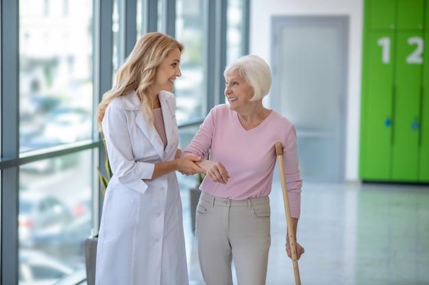 Позитивный врач в лабораторном халате гуляет со старшим пациентом