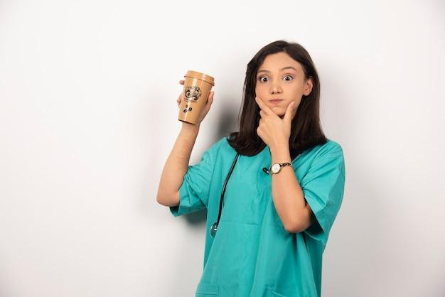 白い背景の上のカップを保持聴診器を持つポジティブドクター。