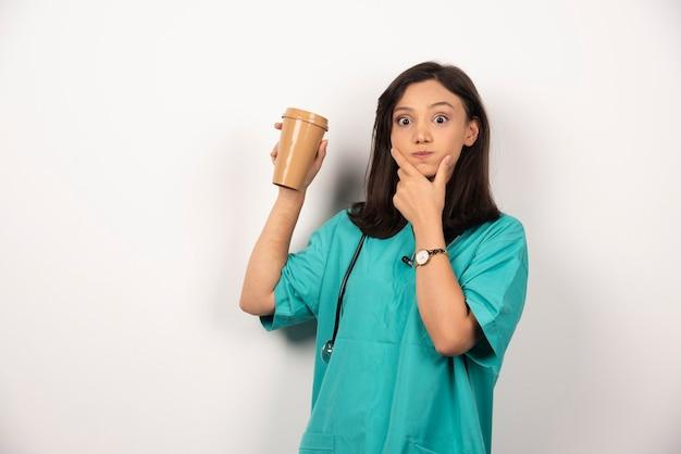 Medico positivo con lo stetoscopio che tiene tazza su priorità bassa bianca. foto di alta qualità