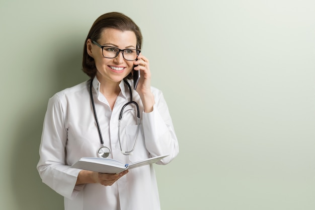 Positive doctor woman talking mobile phone