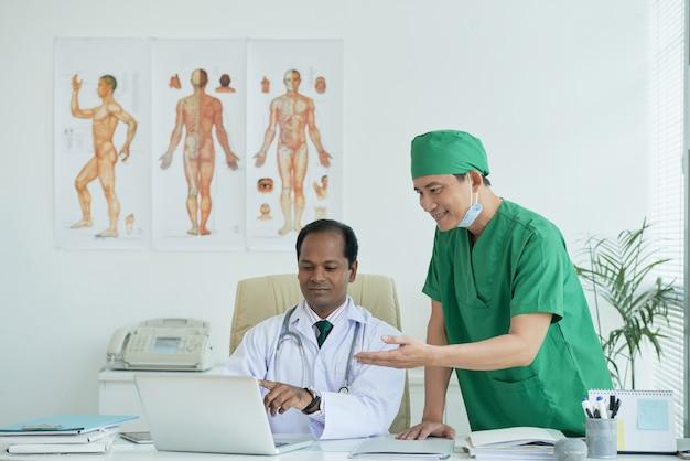 Позитивные врачи обсуждают историю болезни пациента на экране ноутбука