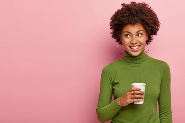Позитивная мечтательная женщина-модель позирует с кофе на вынос, согревается горячим напитком, смотрит налево, ведет непринужденную беседу
