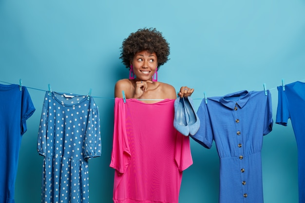 Positive dreamy woman with curly hair stands naked and covers with dress hanging on rope, holds blue shoes, tries to find outfit to fit, dresses for special occasion. people, style, clothing concept