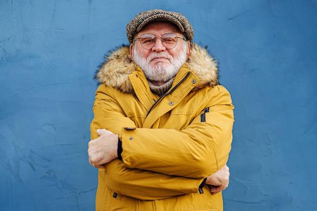 屋外で凍結するポジティブな老人のひげを生やした男。スタイリッシュなアウタークロスアームの年配の男性