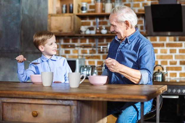 ポジティブな老人と彼の孫が台所に座ってシリアルを食べる