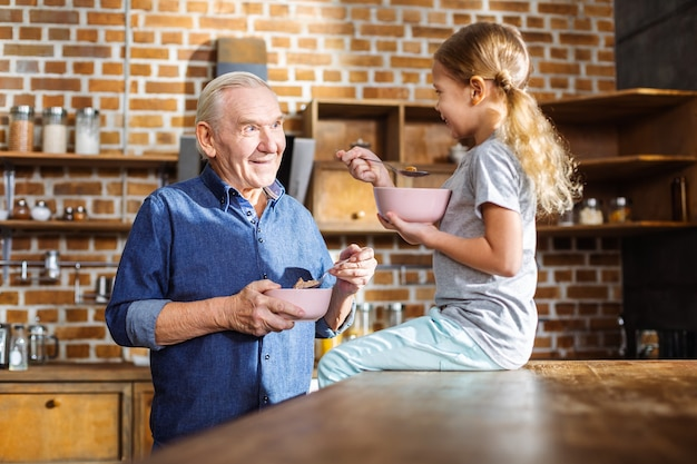 彼の孫娘との時間を楽しみながらシリアルを食べるポジティブな老人