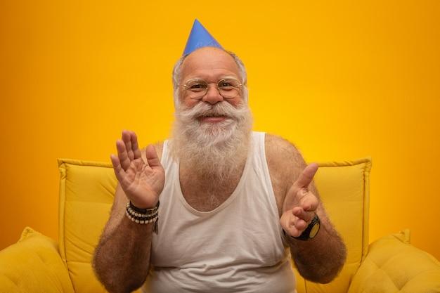 Положительный пожилой человек в шляпе партии, улыбаясь в камеру