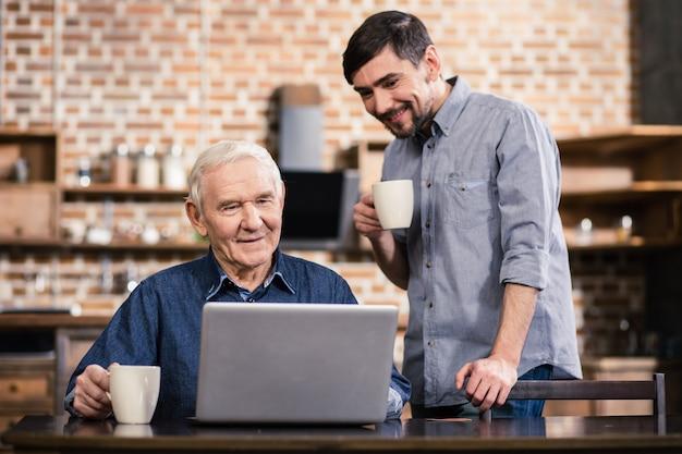Позитивный пожилой мужчина использует свой ноутбук, пока его сын стоит рядом