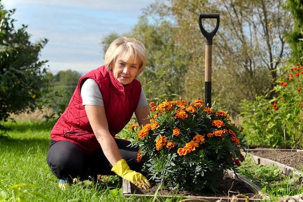 Позитивная пожилая женщина-садовник, работающая в саду